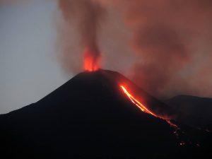 Il nuovo cratere sud-Est in eruzione la sera del 12 agosto 2014, con attività stromboliana da diverse bocchette al vertice del cono e emissione di un flusso di lava da una bocchetta sul suo fianco est. Vista da Santa Venerina, al ese del vertice